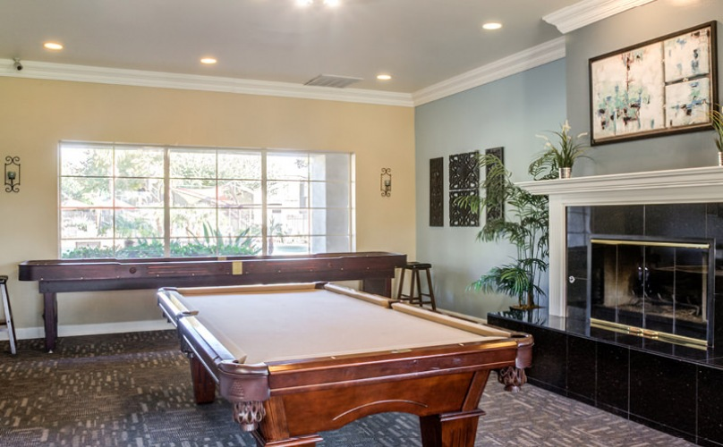 Game room with shuffle board and pool table.