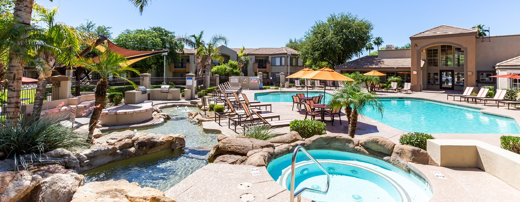 Large pool with hot tub and pool side seating with umbrellas.
